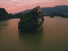 Flying over  rocky island in lake with sunset tinting Stock Footage