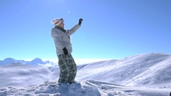 Woman snowboarder makes selfie at the top of the mountain Stock Footage