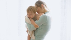 Slow motion portrait of happy mother with cute baby boy at big window in house Stock Footage