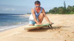 A surfer waxing board before surfing Hawaii Stock Footage