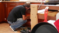 Plumber man with tools in the kitchen. Plumbing and renovation Stock Footage