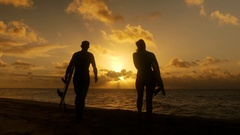 Surfer couple in silhouette holding long surfboards at sunset on tropical beach Stock Footage