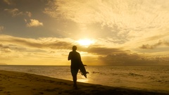 Young surfer on the beach waiting for perfect waves at sunset Stock Footage