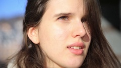 Close up of young woman looking to camera, hair blowing in wind Stock Footage