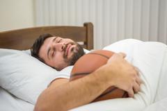 The happy man lay on the bed with a ball Stock Photos
