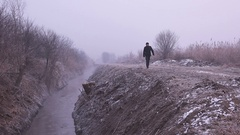 Environmentalist walking by wastewater channel on cold winter day Stock Footage