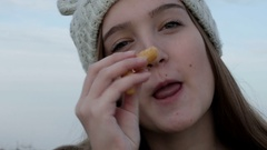 Portrait of a teenage girl in a knitted cap, which showing and eating Israeli Stock Footage