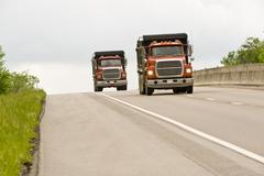 Two Dump Trucks On Highway Stock Photos