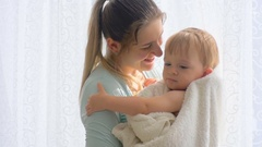 Slow motion closeup shot of happy mother cuddling her baby after having bath Stock Footage