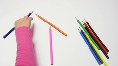 Children hand construct house from pencils on a sheet of paper Stock Footage