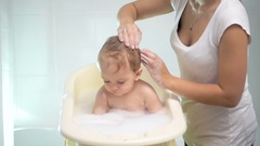 Slow motion of mother washing baby's head with shampoo Stock Footage