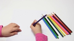 Girl draws pencil flower, cranking Stock Footage