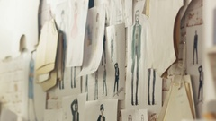 Zoom In On a Wall with Pinned Fashion Drawings and Sketches, Templates Hanging  Stock Footage
