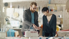 Female and Male Fashion Designer Choosing Sketches for Clothing  Collection Stock Footage