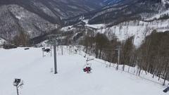 Ski resort, chair ski lift elevator lifting people on the mountain ski slope Stock Footage