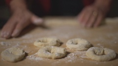 Woman chef preparing donuts bagels on a wooden table covered in flour. Top view. Stock Footage
