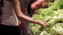 Young family of mother and little daughter choosing vegetables in supermarket. Stock Footage