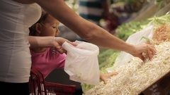 Young family of mother and little daughter picking a bean sprout in supermarket. Stock Footage