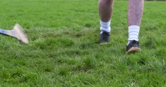Hurling player strikes ball past opposition tackle. Slow Motion Stock Footage