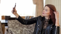 Girl in a black leather jacket makes a selfie sitting in a cafe. Stock Footage