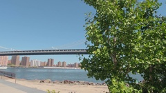LOW ANGLE VIEW: Manhattan Bridge viewed from Empire Fulton Ferry State Park Stock Footage