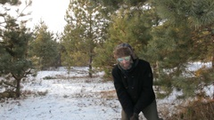 Strange man in a hipster sunglasses with beard throws an ax to a tree. Woman in Stock Footage