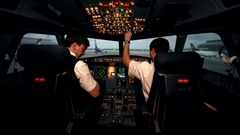 Co-pilot in the flight deck of a passenger aircraft turn on avionics and shows Stock Footage