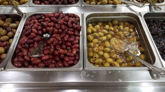 Variety of olives in an olive bar sold in the grocery store Stock Footage