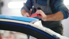 Automobile service - a worker polishes a blue car, front view Stock Footage