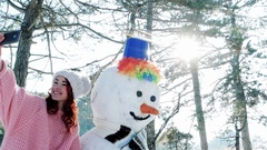 Winter selfie, cute girl making photo with snowman, a mobile phone in the hand Stock Footage