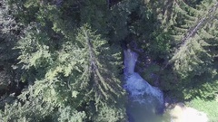 AERIAL: Mountain river flowing through lush forest cascading over rocky wall Stock Footage