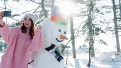 Cute girl making photo with a snowman, winter selfie, mobile phone in hand of a Stock Footage