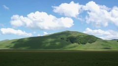 White clouds moving over mountains, Castelluccio of Norcia. Sunny day in Umbria Stock Footage