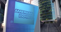 Street signage board with American Express logo. Modern office center skyscraper Stock Footage