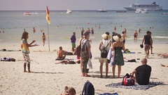 Tourists Enjoy the Sun and Tropical Sea with Cruise Ship in the Background Stock Footage