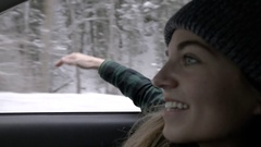 Profile Of Young Woman Sitting In Passenger Seat, Smiles, Holds Arm Out Window Stock Footage