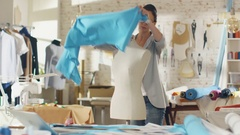Beautiful Female Fashion Designer Adjusting Fabrics on a Tailored Mannequin.  Stock Footage