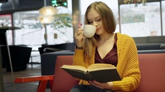 Girl in yellow sweater reading book in the cafe and drinking coffee Stock Footage