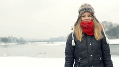Happy girl standing in the wintry park by the river and looks thoughtful Stock Footage