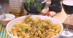 Grating parmesan cheese over Italian pasta (penne) with pesto sauce Stock Footage