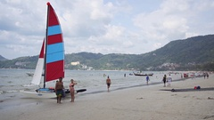 Tiny Catamaran Sailboat for Rent on Crowded Patong Beach Stock Footage
