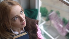 Close-up, portrait of a beautiful girl with a book that looks out the window and Stock Footage