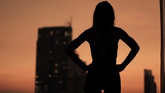 Silhouette of woman admire cityscape view at night Stock Footage