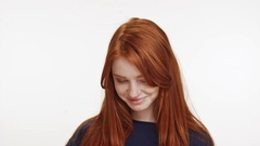 Shy coy ginger Caucasian teenage girl standing smiling on white background Stock Footage