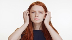 Young beautiful Caucasian red-haired girl peering at camera with displeasure on Stock Footage