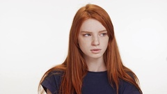 Outraged red-haired Caucasian teenage girl standing on white background looking Stock Footage