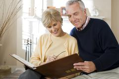 Mature couple looking at photo album Stock Photos