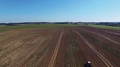 4K. Aerial. Harvesting potatoes with modern potato-digger trailer and tractor. Stock Footage