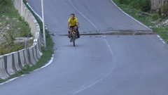Cyclist riding on a paved road Stock Footage
