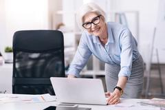Delighted aged businesswoman working in the office Stock Photos